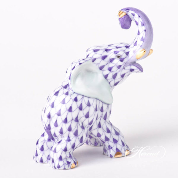 "Elephant figurine is painted in Vieux Herend (VHL) Lilac fish scale design. This fishnet or fish scale pattern is a typical motif of Herend. It can be ordered in 14 different VH (fishnet/fish scale) colors. Zoological description: Touching is an important form of communication among elephants. Individuals greet each other by stroking or wrapping their trunks; the latter also occurs during mild competition. The older elephants use trunk-slaps, kicks and shoes to discipline younger ones. Touching is especially important for mother–calf communication. Figurine data Height: 8.5 cm (3.5""H) Width: 4.7 cm (2""W) Length: 8 cm (3.25""L) Weight: 0.09 kg"